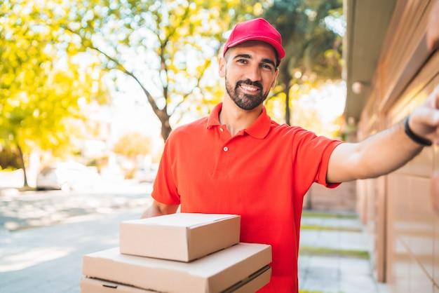 家のドアベルを鳴らしている段ボールのピザボックスを持つ配達人の肖像画。配送と配送サービスのコンセプト。
