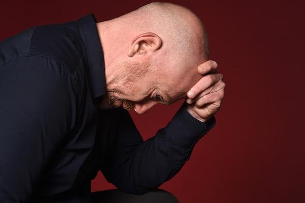 Портрет отчаявшегося человека на красном фоне