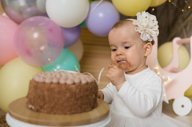 앉아 케이크를 먹고 축제 의상에 더러운 어린 소녀의 초상화