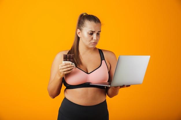 Портрет разочарованной полной молодой женщины в спортивной одежде, стоящей изолированно над желтой стеной, используя портативный компьютер, держа плитку шоколада
