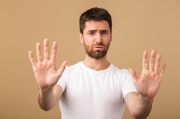 Портрет разочарованного молодого человека, небрежно одетого, демонстрирует жест стоп, изолированный на бежевом