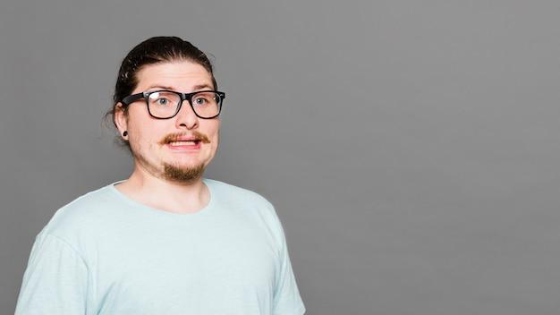 Портрет отвращения молодого человека на сером фоне