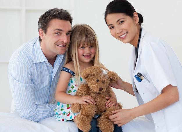 テディベアを検査している医者と幸せな少女の肖像