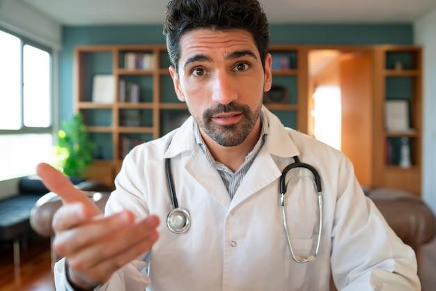 Портрет врача во время видеовстречи с пациентом по видеосвязи. новый нормальный образ жизни. концепция здравоохранения и медицины.