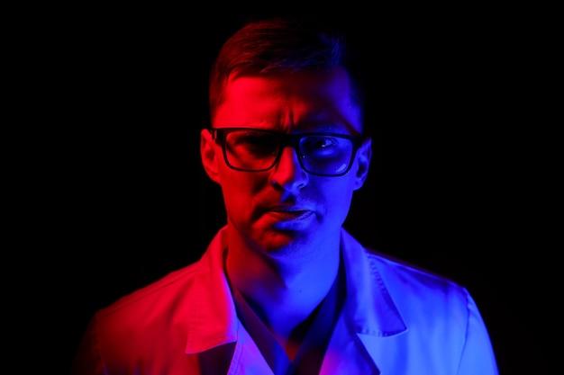 医師または医療専門家の肖像画。横長のフルサイズのポートレート。スクラブの男。青と赤の光と黒の背景。閉じる。