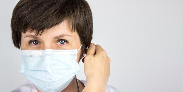 의사의 초상화, 수술용 마스크를 제거하고 닫습니다. 코로나 종식. 잠금 종료