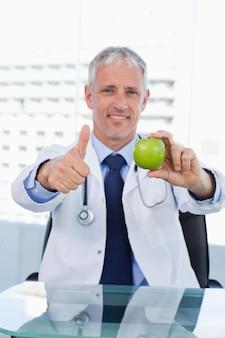 親指でアップルを示す医師の肖像