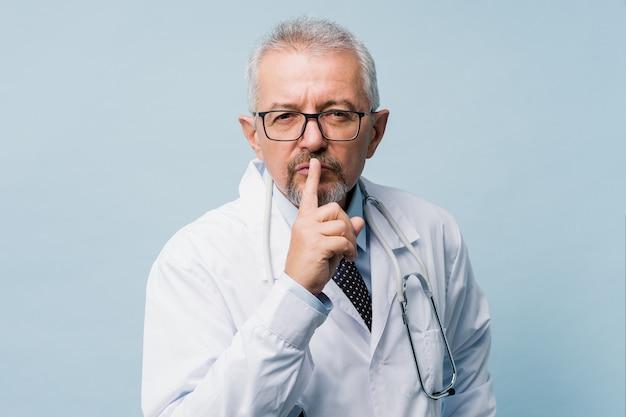 Портрет доктора показывая жест безмолвия. медицинская тайна концепция.