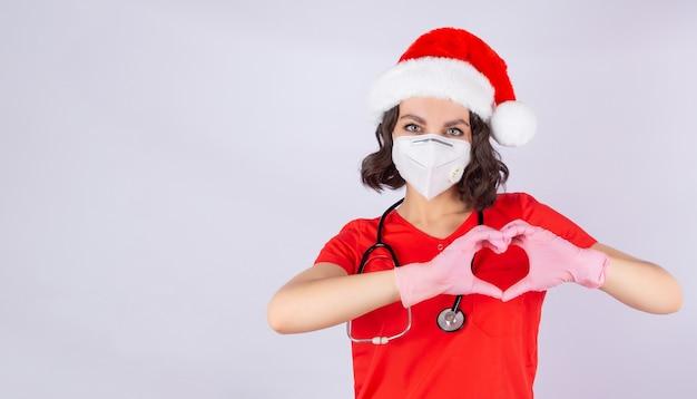 健康な心臓を示す医療保護マスクサンタ帽子とピンクのニトリル手袋の手で医者の女の子の肖像画