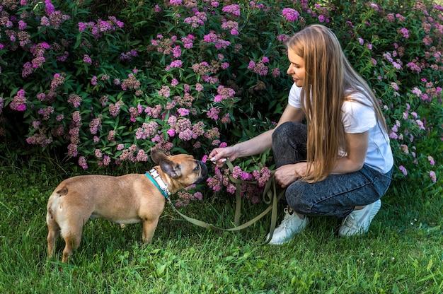 Портрет собаки и молодой женщины в парке на фоне цветов летом