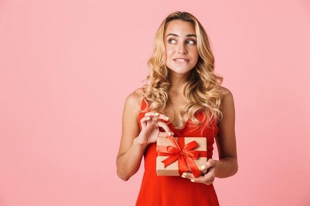 Портрет мечтающей довольно молодой милой белокурой женщины, позирующей изолированной над розовой стеной, держащей подарочную коробку.