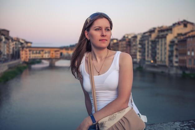 Портрет мечтать молодая белая девушка, сидя на мосту реки во флоренции, италия.