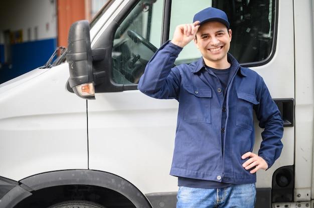 Портрет водителя, стоящего возле своего фургона и улыбающегося