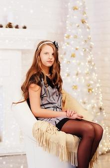 Портрет элегантной довольно длинноволосой девушки-подростка в платье с елочными украшениями