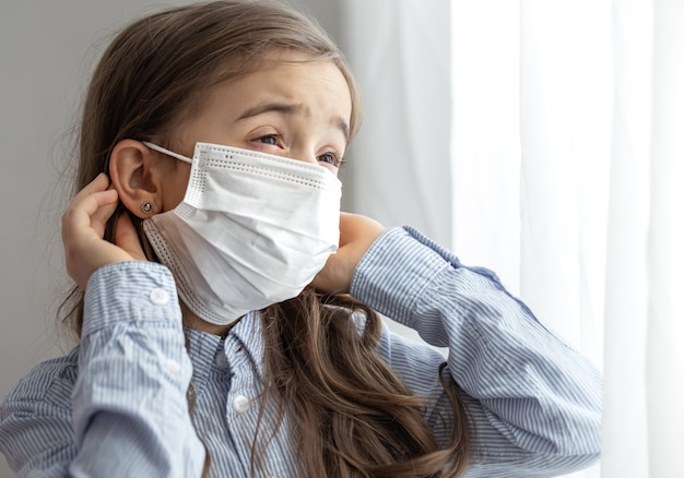 Портрет девочки начальной школы в защитной одноразовой маске. концепция детства во время пандемии и карантина.