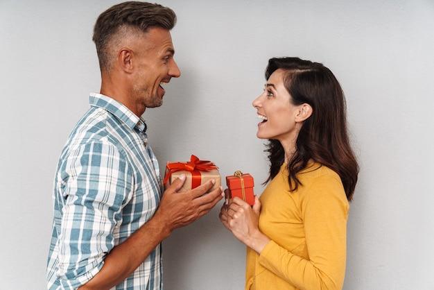 Портрет эмоционально потрясенной удивленной милой оптимистичной взрослой влюбленной пары, изолированной над серой стеной, держащей подарки друг для друга