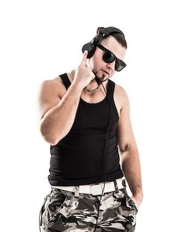 Портрет энергичного парня рэпера в темных очках и с наушниками на светлом фоне