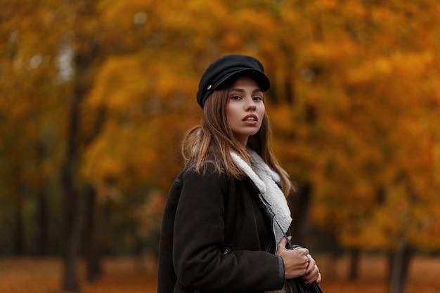 森のオレンジ色の葉を背景に暖かい茶色のスタイリッシュなジャケットのバイザーと流行の帽子をかぶったヨーロッパの若い女性の肖像画。かわいい女の子。女性のカジュアルアウターの新しいコレクション。