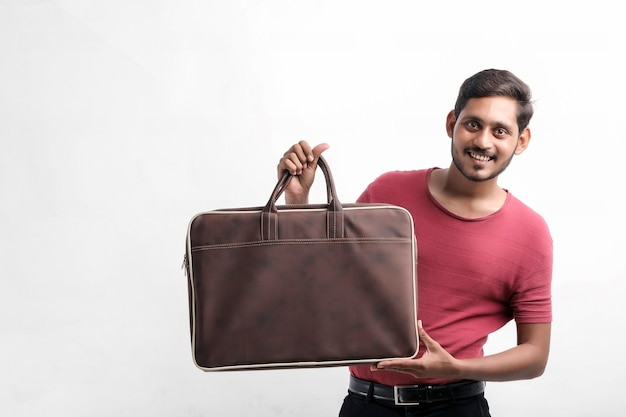 白い背景の上に立って、手にバッグを持ってキャップで興奮して幸せな若い配達人の肖像画。