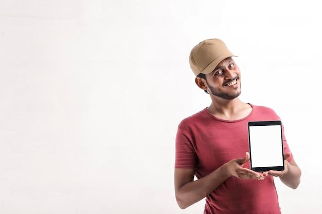 白い背景の上に立っている帽子の興奮した幸せな若い配達人の肖像画。携帯電話のディスプレイを示すカメラを探しています。