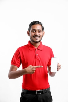 赤いtシャツと白い背景の上のスマートフォンを示す興奮した幸せな若い配達人の肖像画。