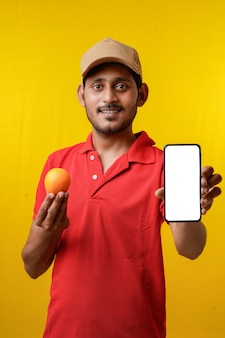 赤いtシャツを着て、黄色の背景にスマートフォンを表示している興奮した幸せな若い配達人の肖像画。