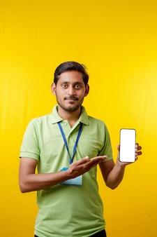 Tシャツを着て、黄色の背景にスマートフォンを表示している興奮した幸せな若い配達人の肖像画。