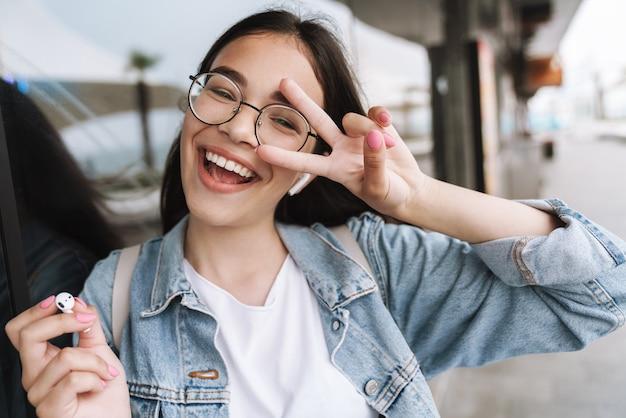 Портрет взволнованной счастливой молодой красивой студентки в очках гуляет на открытом воздухе, отдыхая, слушая музыку с наушниками, показывая жест мира