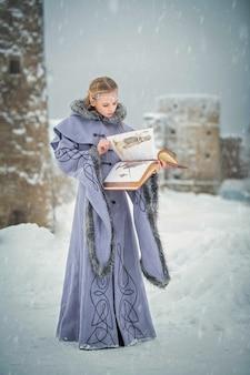 Портрет сказочной эльфийки с волшебной книгой в руках на фоне зимней природы и волшебной крепости