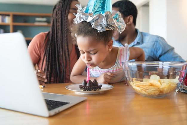 Портрет семьи, празднующей день рождения в режиме онлайн во время видеозвонка, оставаясь дома.