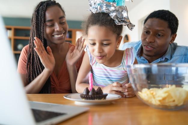 Портрет семьи, празднующей день рождения в сети, во время видеозвонка с ноутбуком, оставаясь дома