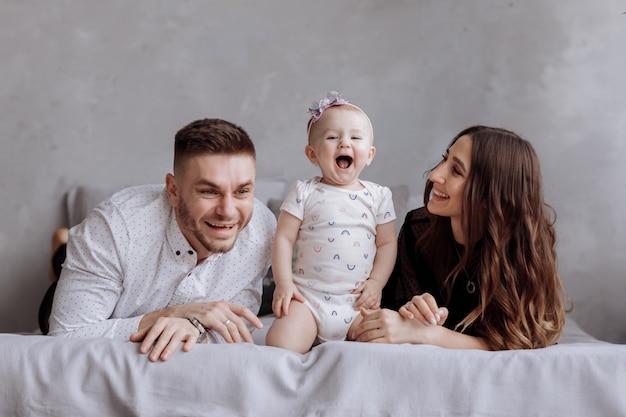 Портрет семьи на кровати дома во время игры с их девочкой - отец, мать и годовалая маленькая дочь весело проводят время вместе - момент близости - копирование пространства