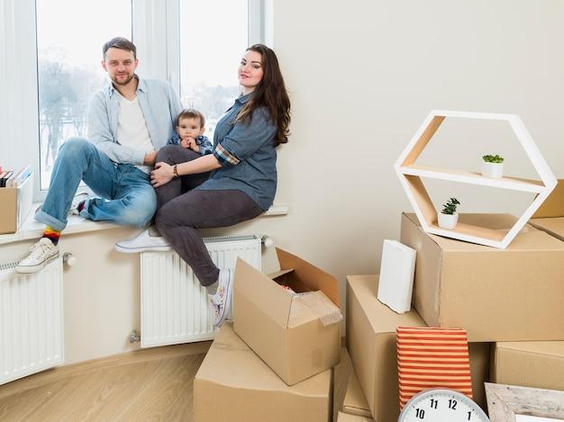그들의 새로운 가정에서 골판지 상자를 움직이는 가족의 초상