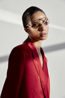 彼女の顔と赤いジャケットにアクセサリーを持つファッショナブルな女性の肖像画