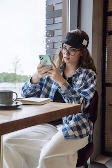 카페에 앉아 전화를 사용하여 인터넷에서 통신하는 세련된 세련된 여성의 초상화