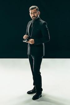 黒の上にポーズをとって流行のスーツを着てスタイリッシュなヘアカットを持つファッショナブルな若い男の肖像画。