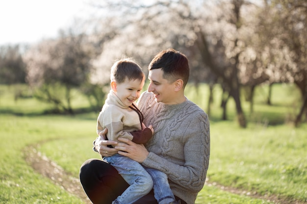 春の花の木を背景にニットセーターの父と息子の肖像画。