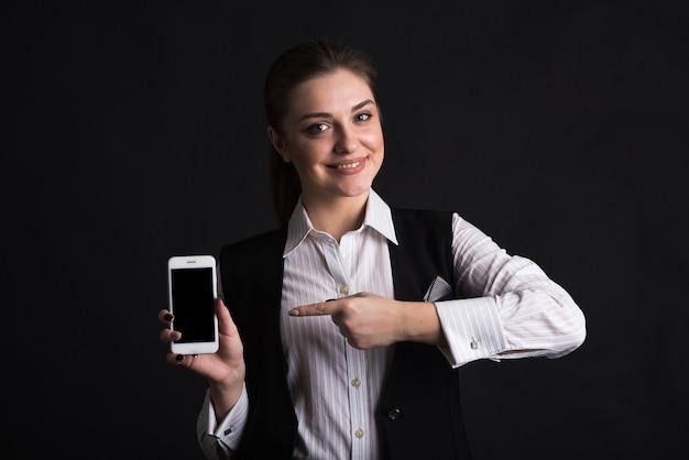 Портрет женщины-бизнес-леди, которая указывает пальцем на экран своего смартфона