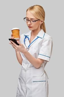 Портрет женщины-врача, держащей бумажный стаканчик с кофе и разговаривающей по телефону