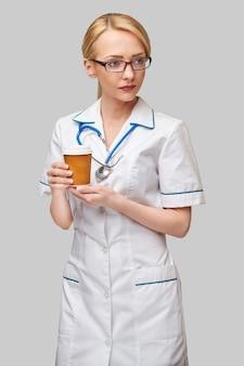 コーヒーの紙コップを保持している女性医師の肖像画