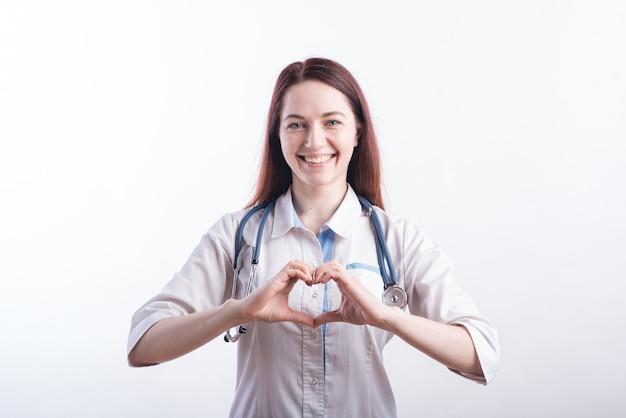Портрет женщины-врача в белой форме, демонстрирующей жест любви