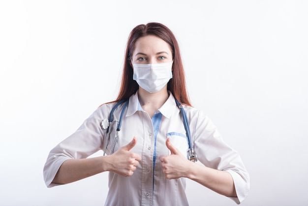 Портрет женщины-врача в белой форме, которая показывает одобрительный жест большим пальцем вверх в студии на белом фоне