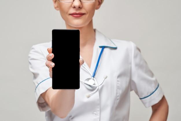 空白の画面で携帯電話を保持し、表示している女性医師または看護師の肖像画