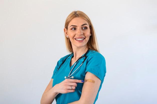 ワクチン接種後に笑っている女性医師の肖像画。予防接種を受けた後、包帯で腕を見せている医療従事者。