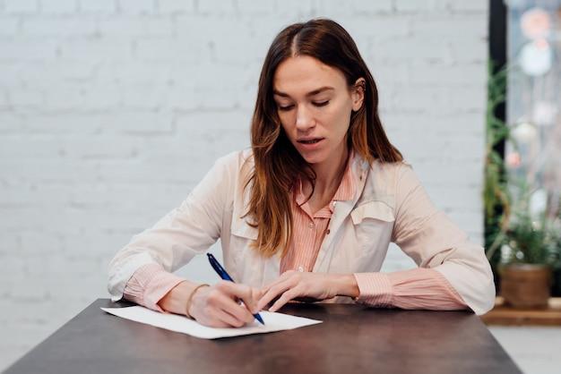 彼女の机で書いている女性医師の肖像画。