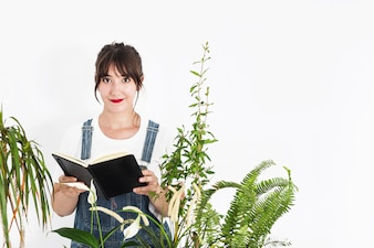 Portrait of a female florist holding diary on white background