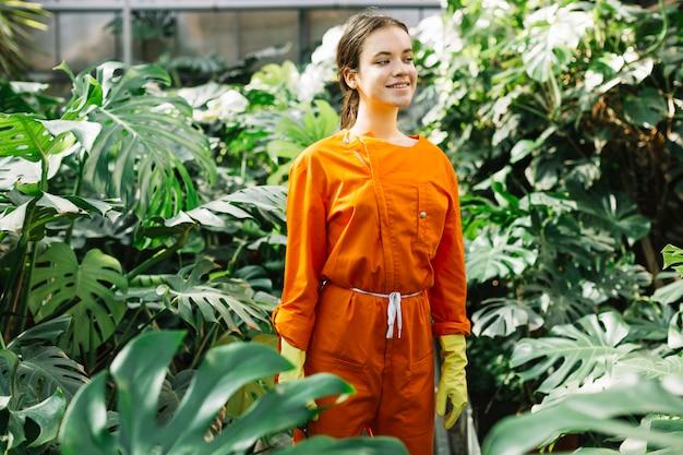 Портрет женщины-садовника в рабочей одежде, стоящей в теплице