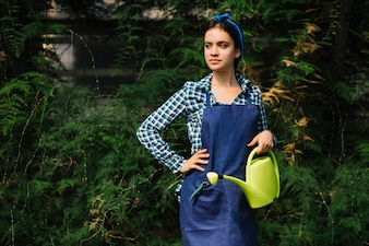 Portrait of a female gardener with watering can