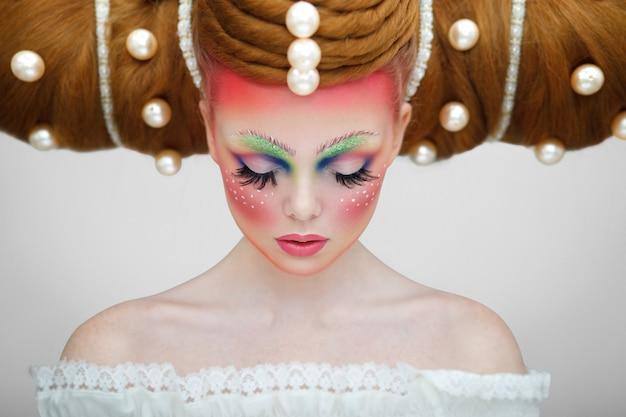Портрет девушки-модели с творческим красочным макияжем и прической с огромным жемчугом.
