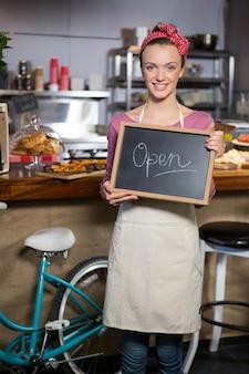 オープンサインを保持している女性スタッフの肖像画